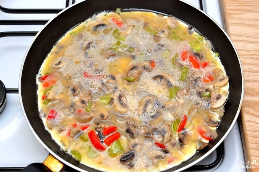 Жарьте омлет с овощами с обеих сторон.