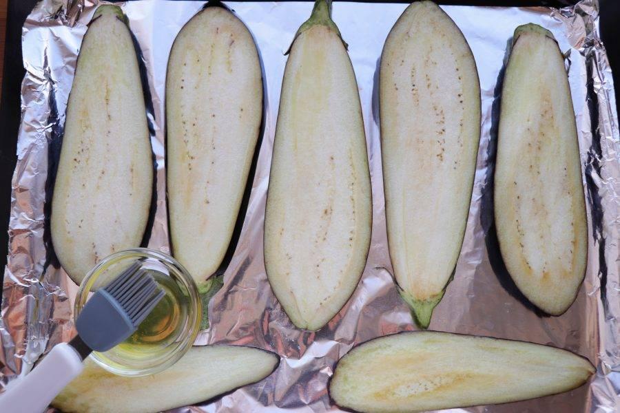 Нарезанные баклажаны выложите на смазанный маслом противень, смажьте их также маслом сверху и запекайте в разогретой до 200 градусов духовке около 15 минут. Баклажаны должны стать золотистыми и мягкими.