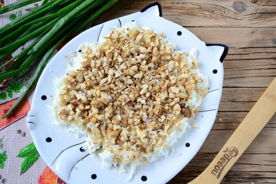 Орехи измельчите в блендере до состояния крошки или просто порубите широким ножом. Выложите орехи вторым слоем.