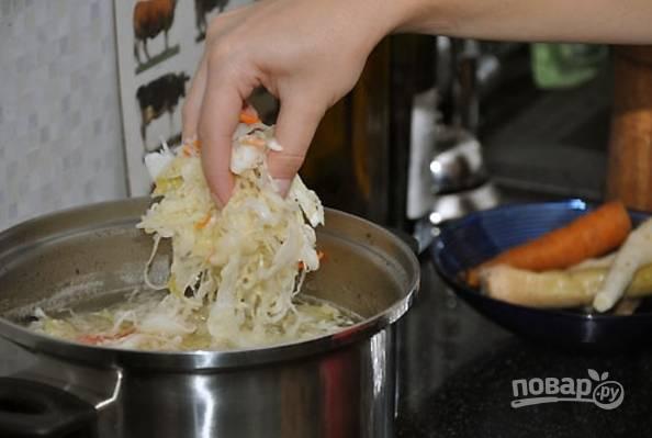 3.Спустя необходимое время достаньте из бульона мясо, все овощи, лавровый лист. Разберите мясо на кусочки и сразу верните его обратно, добавьте квашеную капусту и доведите до кипения, варите полчаса.