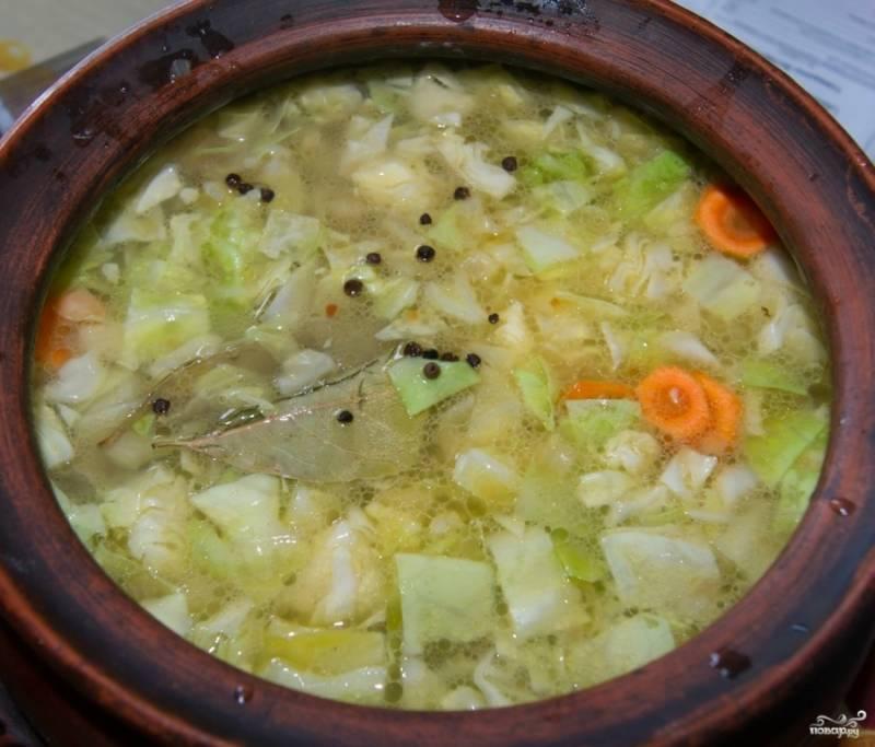 3. Подготовленные овощи (картошку и капусту нарежьте кубиками, морковь — кружочками) и обжаренное мясо выложите в глиняный горшочек, залейте горячим бульоном. Бульон предварительно заправьте немного обжаренной на сухой сковороде мукой.