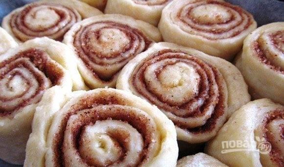 Раскатайте тесто, размером 30х40 см и толщиной в 5 мм. Сделайте начинку из смеси сахара с корицей. Смажьте тесто с одной стороны маслом и смесью, отступив от одного края в 3 см. Сверните пласт теста в рулет, затем нарежьте на порционные булочки. Накройте полотенцем и оставьте на 15 минут в тёплом месте. Запекайте изделия в горячей духовке при 180 градусах в течение 15-20 минут.