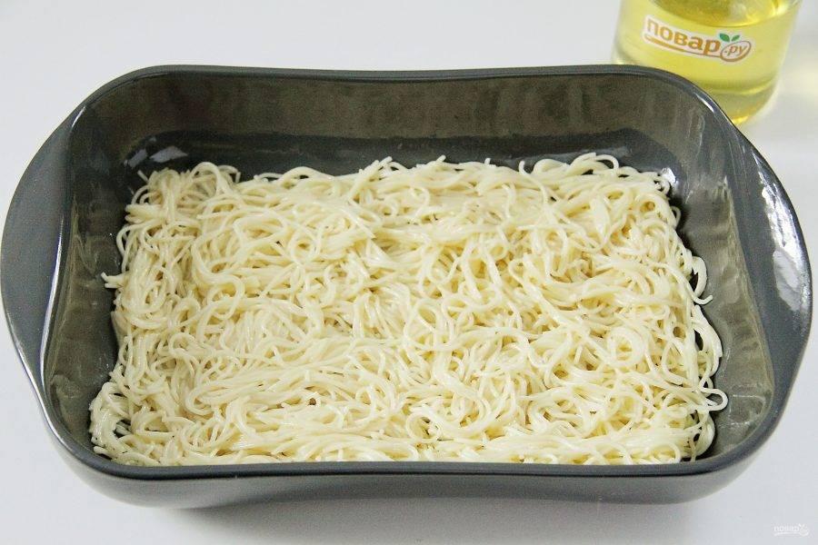 Форму для запекания смажьте маслом. В макароны добавьте яйца, перемешайте и выложите 1/2 часть ровным слоем.