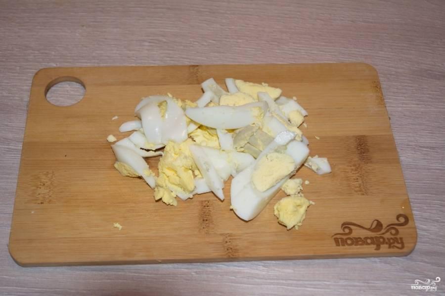 Отварные куриные яйца нужно нарезать мелким кубиком. Соедините все подготовленные продукты в салатнике и перемешайте.