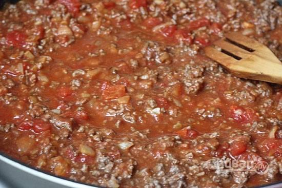 3. Добавьте в соус фарш. Посолите, поперчите, добавьте специи. Влейте оставшийся томатный соус и потушите 10-15 минут.