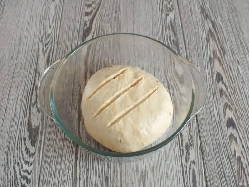 Форму для выпечки смажьте растительным маслом. Выложите округленное тесто. Сделайте три разреза. Оставьте на 40 минут для подъема. Разогрейте духовку до 230 градусов, поставьте форму с водой. После поставьте выпекаться хлеб на 10 минут. Через указанное время достаньте форму с водой, уменьшите температуру до 180 градусов и выпекайте еще 25-30 минут.