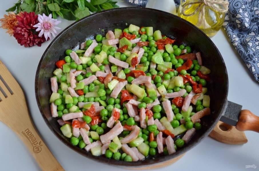 Разогрейте на сковороде 2 столовые ложки оливкового масла. Обжарьте ветчину. Добавьте цукини, вяленые помидоры, обжарьте. Зеленый горошек погрузите на минуту в кипяток, после чего сразу в ледяную воду (для сохранения цвета), потом положите в сковороду к остальным овощам и прогрейте, перемешайте.