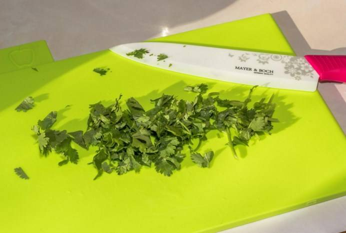Нарежьте зелень кинзы.