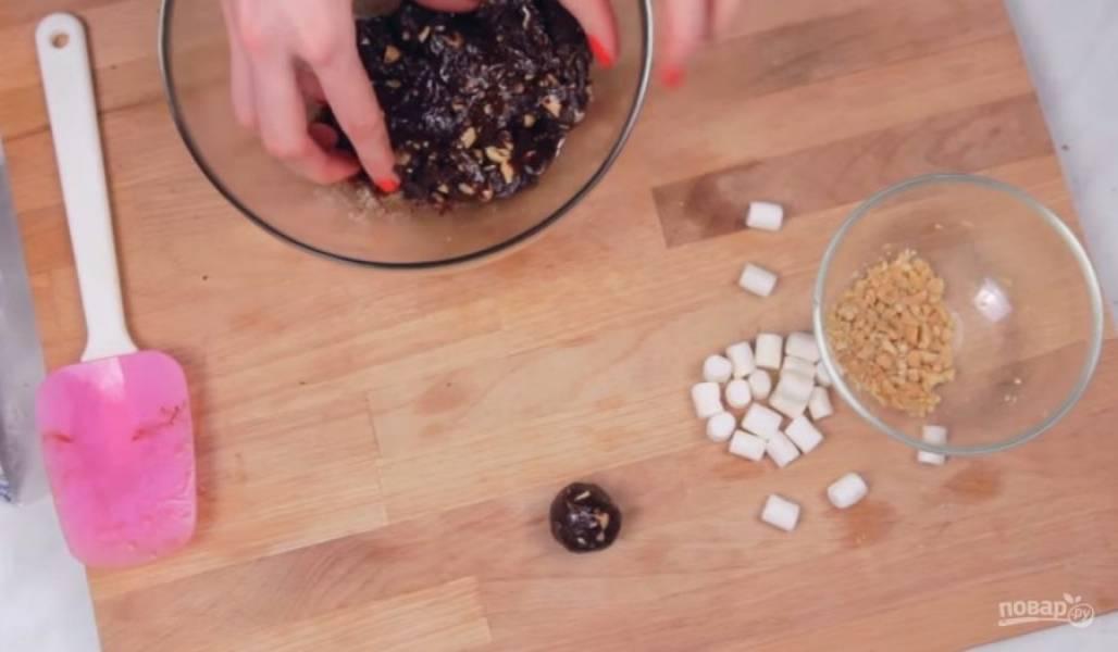 2.  Затем снимите массу с огня и добавьте в нее измельченные орехи с маршмеллоу. Добавляйте начинку до тех пор, пока масса не станет однородной и пока не загустеет.