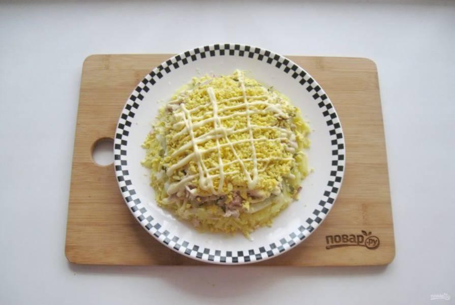 Яйца сварите вкрутую, охладите, очистите. Отделите желтки от белков. Натрите желтки на терке и выложите на слой курицы. Покройте майонезом.