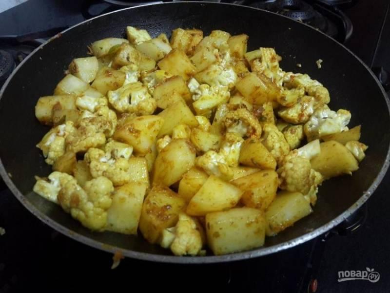 2. В сковороде обжарьте семена фенхеля, имбирную и чесночную пасту, чили. Протушите овощи в течение 3х минут. После чего поместите в сковороду нарезанный кубиками картофель и цветную капусту. Приправьте тмином и куркумой. Тушите овощи до золотистого цвета.