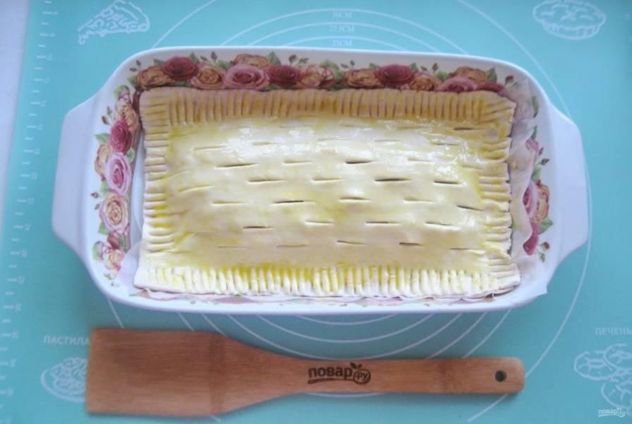 Выложите пирог в форму для выпекания. Смажьте взбитым яйцом.