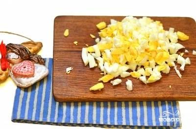 2.Заранее отварите яйца вкрутую. Охладите их, почистьте от скорлупы, нарежьте кубиками и добавьте в салат.