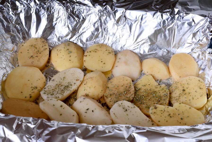 Когда мясо замаринуется, берем довольно широкую форму для запекания и застилаем ее в несколько слоев фольги (5-6 примерно). Выкладываем на фольгу ровный слой картофеля, сбрызгиваем его оливковым маслом, посыпаем специями и солью.
