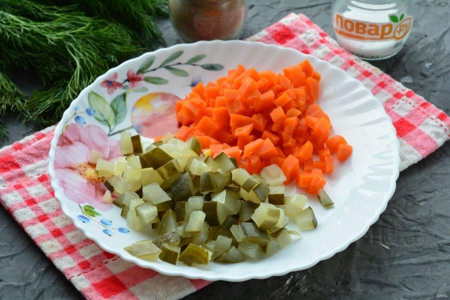Сварите морковку, она варится примерно столько же времени, как и картошка. Почищенную морковку нарежьте кубиками. Также нарежьте и соленые огурцы.