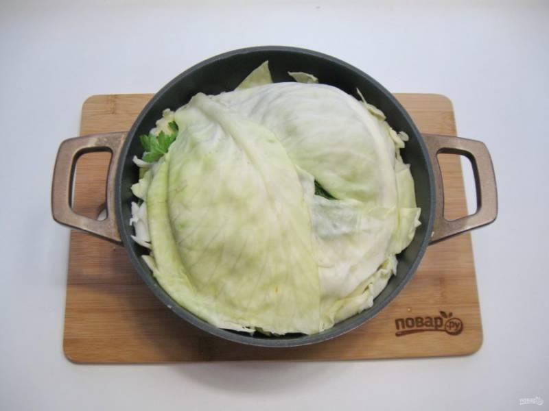 Накройте мясо с овощами листами капусты. Накройте казан крышкой и поставьте груз. Это может быть банка с водой или просто что-то тяжелое.  Благодаря этой процедуре овощи выделят много сока.