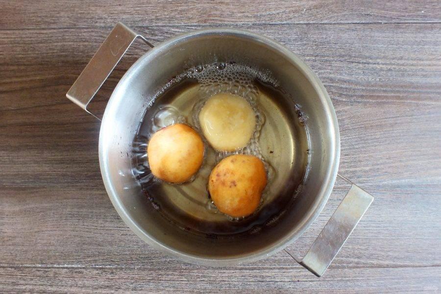 В кастрюле разогрейте растительное масло, огонь убавьте до чуть ниже среднего. Опустите подготовленные пончики. Обжаривайте со всех сторон, периодически переворачивая.