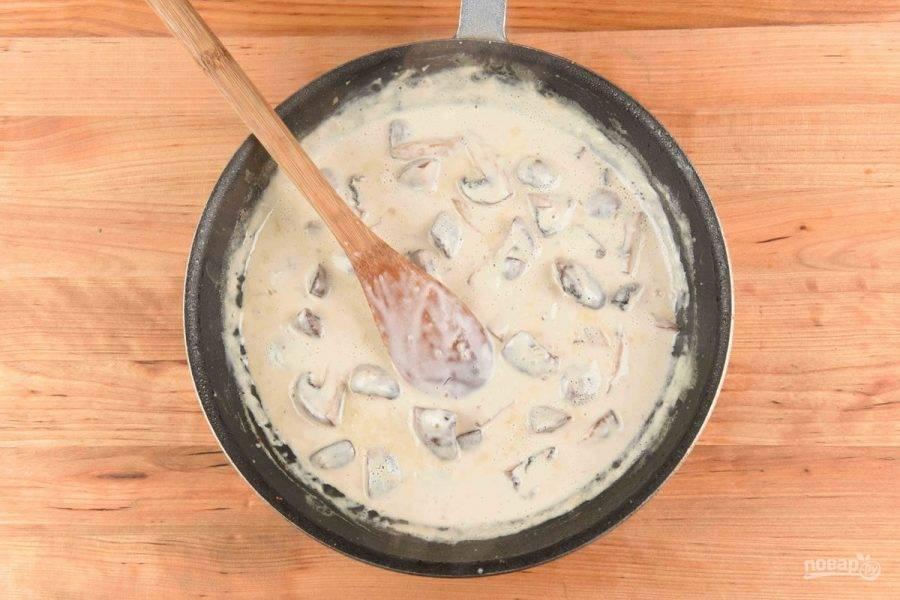 4. Тем же временем сделайте соус. В разогретом масле обжарьте грибы в течение минуты. Добавьте чеснок и лук. Готовьте ещё 30 секунд. Затем влейте вино и сок половины лимона. Тушите 2 минуты. И, наконец, добавьте сметану и воду из-под пасты. Доведите соус до кипения, а потом варите 5 минут, помешивая.