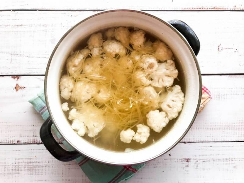 В бульон выложите мелко нарезанную цветную капусту, вермишель, перемешайте и варите 15 минут.