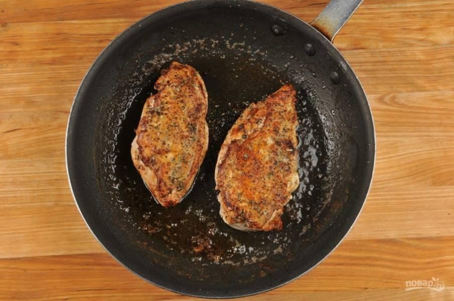 2. Курицу смажьте солью, перцем и травами. Затем обжарьте её в разогретом масле на сковороде с каждой стороны по 4 минуты.