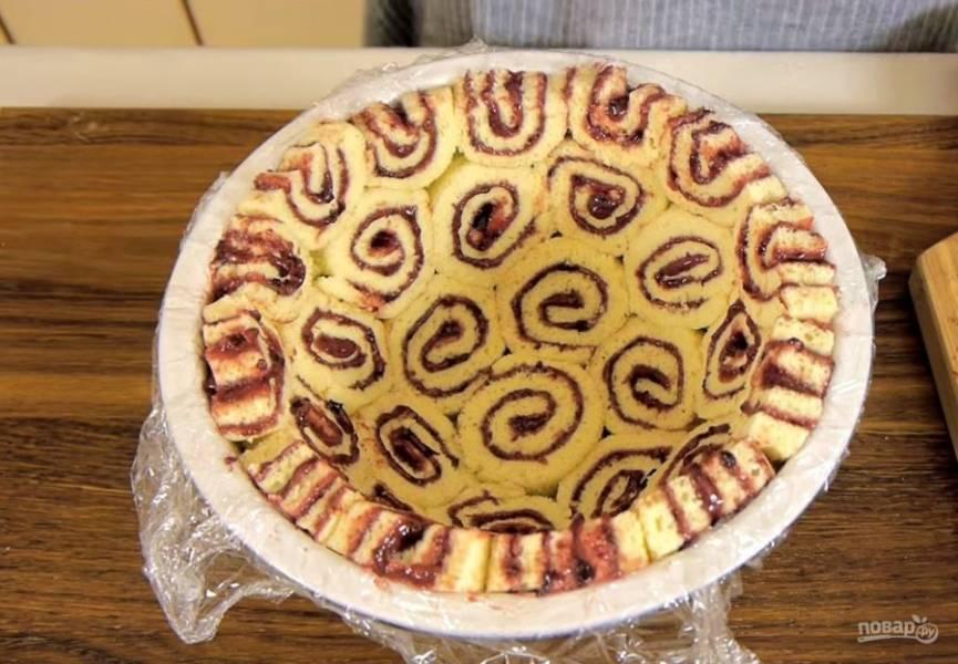 4. Желатин залейте холодной кипяченой водой, перемешайте и оставьте для набухания. Миску для торта выстелите пищевой пленкой. Выложите поверхность миски рулетом, нарезанным на кружочки толщиной 1,5-2 см, плотно прижимая кусочки друг к другу.