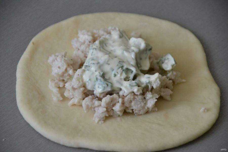 Раскатайте из теста лепешку, в центр которой положите обжаренный куриный фарш, сверху чайную ложку майонеза.