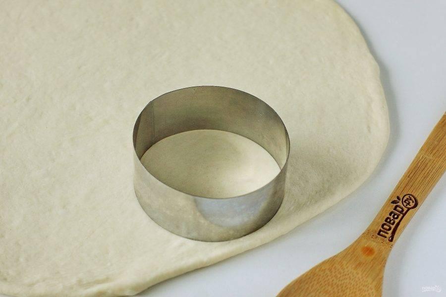 Тесто нужно обмять и на присыпанной мукой поверхности раскатать в пласт, толщиной 1-1,5 см. Металлической вырубкой или обычным стаканом вырежьте круглые заготовки желаемого размера.
