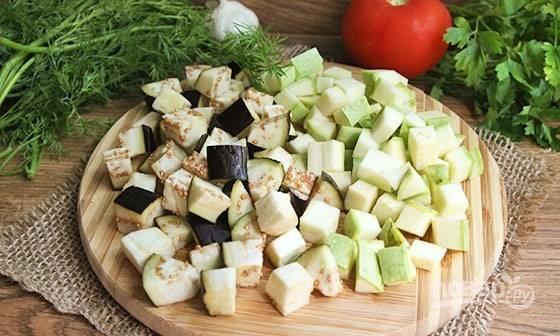 Для начала избавьтесь от горечи баклажана. Нарежьте его крупно, присыпьте солью и оставьте на 15 минут. Затем смойте соль. Потом нарежьте кабачок и баклажан кубиками.