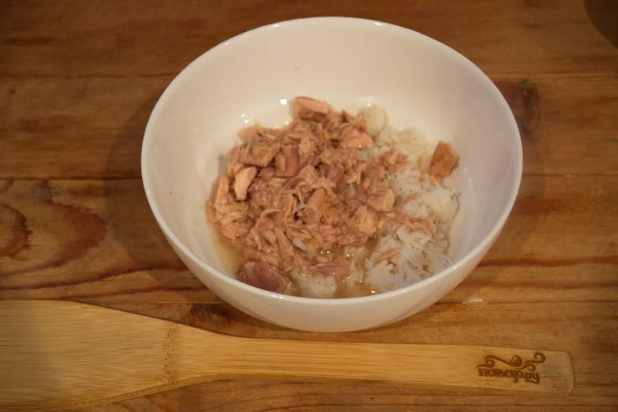 Откройте банку с тунцом. Жидкость слейте. Мясо тунца нужно слегка размять вилкой. Выложите его в миску. Добавьте отварной рис.