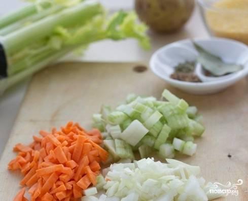 Морковку поскоблите ножиком и вымойте. Нарежьте ее кубиками или небольшими брусочками. Сельдерей также промойте водой и нарубите мелко. Лук освободите от шелухи. Нарежьте его кубиками.