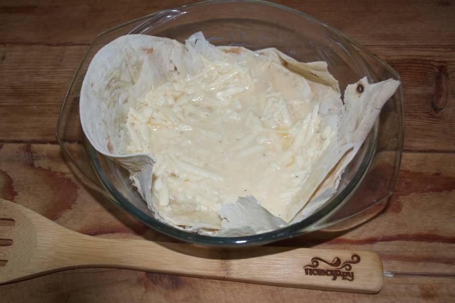 В сырную массу влейте немного молока. Целый стакан молока может и не понадобиться. Консистенция массы должна быть близкой к тесту на пасте. Масса должна быть достаточно жидкой, чтоб хорошо пропитать листики лаваша, но не такой, чтоб сыр полностью погрузился в молоко и скрылся из вида.