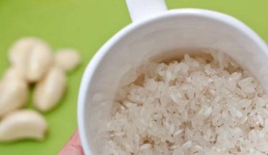 2. Лук и чеснок измельчим и пассируем на растительном масле. Затем добавим к ним хорошо промытый рис и обжарим, рис станет немного румяным. Затем отправим это все в бульон. Туда же - перетертые в пюре томаты. Доводим до кипения.