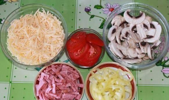 Тем временем подготовим остальные ингредиенты. Сыр натрите на средней терке, помидоры и перец нарезаем кольцами, грибы - пластинками, салями - соломкой.