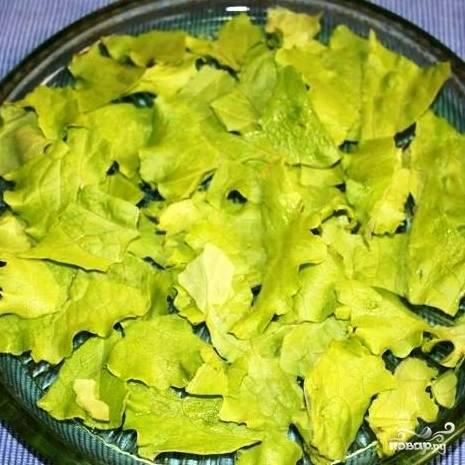 В плоское салатное блюдо выкладываем крупно порванные листья салата.