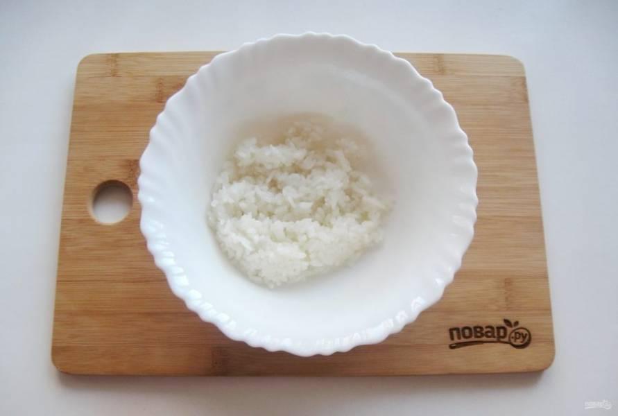 Рис сварите до готовности. Для этого хорошо его помойте и выложите в кастрюлю с  кипящей водой, посолите по вкусу и перемешайте. Соотношение риса к воде 1:2. Варите 10-12 минут. После воду слейте.
