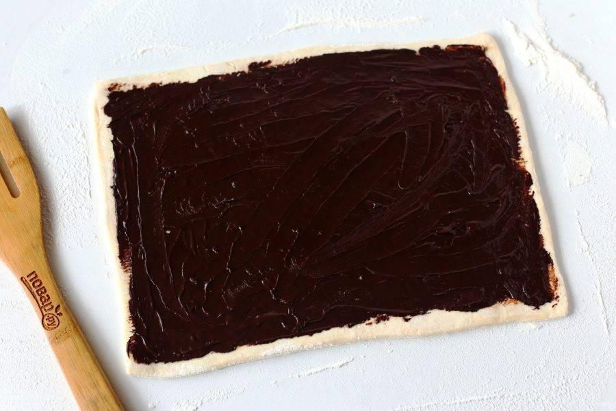 Рабочую поверхность посыпьте мукой. Раскатайте каждый пласт теста в форме прямоугольника и смажьте растопленным шоколадом.