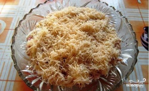 Сыр натрите на мелкой терке. Выложите половину сыра поверх орехов. Повторите все слои заново, завершая все сыром. Слой из сыра также необходимо смазать небольшим количеством майонеза.