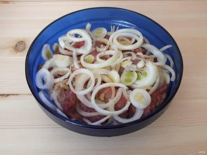 Добавьте нарезанный лук, примерно 2/3 от общего количества. Перемешайте, разминая лук. Оставшийся лук выложите сверху. Подготовленное мясо уберите в холодильник от 1,5 до 3 часов.