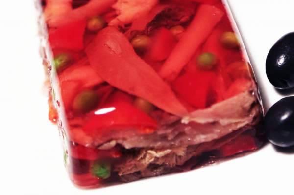 Вынуть из формы заливное и перевернуть на блюдо, подавать с маслинами.