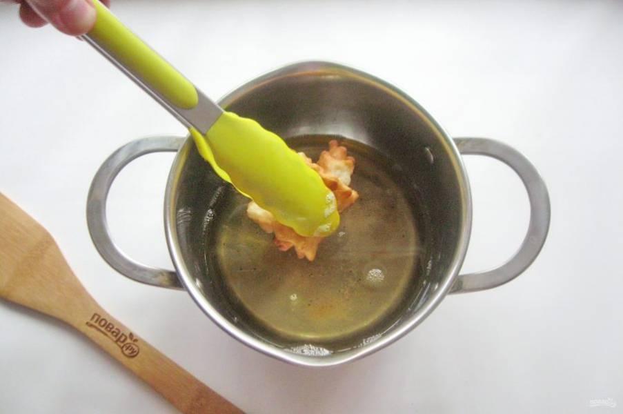 В кастрюлю с толстым дном налейте рафинированное подсолнечное масло и хорошо его нагрейте. Выкладывайте заготовку и сразу же поддерживайте щипцами, чтобы тесто не развернулось в ленту. Так как в процессе жарки тесто раздувается.
