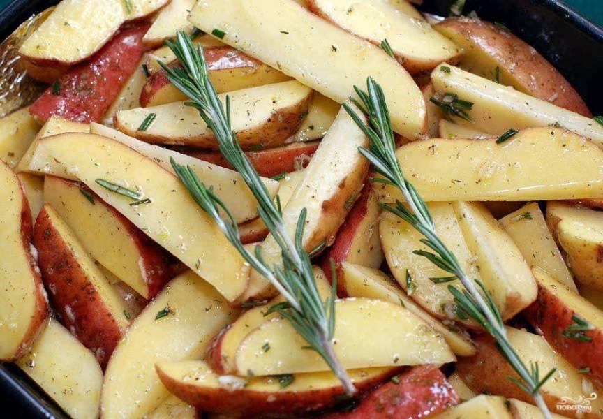 Противень застелите бумагой для запекания. Картофель залейте оливковым маслом и выложите в форму. Сверху положите веточку розмарина, разделив её на две части.
