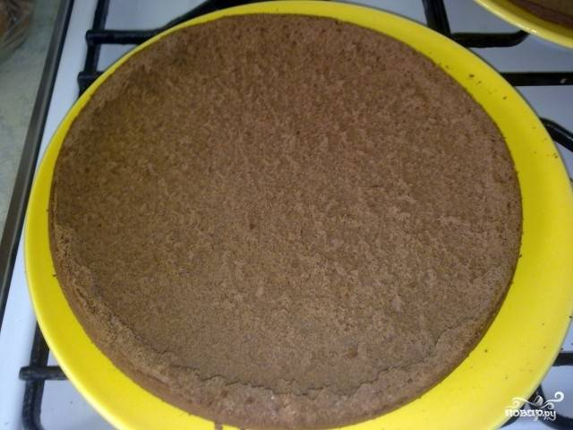 Духовку разогрейте до 180 градусов. Тем временем форму для выпечки коржа хорошо смажьте сливочным маслом и вылейте в неё тесто. Выпекайте корж 40 минут. Главное - первые 30 минут не открывайте духовку. Испечённый корж полностью остудите, а затем разрежьте его поперёк на два одинаковых коржа при помощи длинного острого ножа.