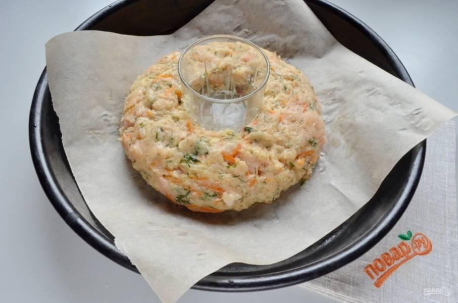 Застелите противень бумагой, поставьте по центру стакан. Столовой ложкой раскладывайте фарш плотно вокруг стакана. Мокрыми руками придайте красивую форму пирогу.