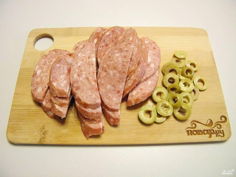 Колбасу порежьте полукольцами, оливки колечками. Вместо зеленых можно использовать черные или оба вида.