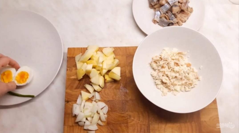 1. Батон нарежьте произвольными кусочками и залейте молоком, чтобы он хорошо пропитался. Возьмите кислое яблоко и снимите с него кожуру, удалите семечки и нарежьте произвольными кусочками. Лук и яйцо тоже нарежьте.