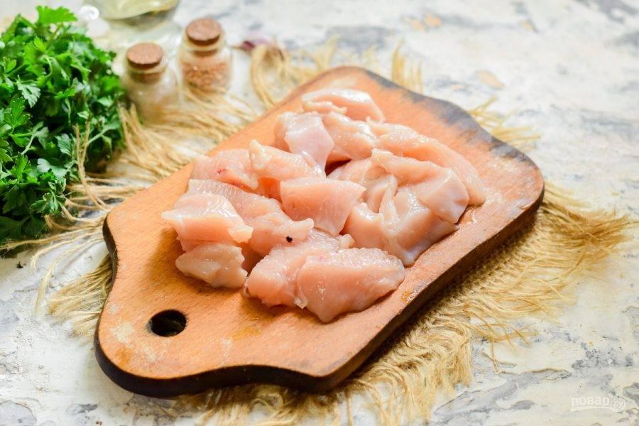 Куриное филе ополосните и просушите, после нарежьте его небольшими кусочками.