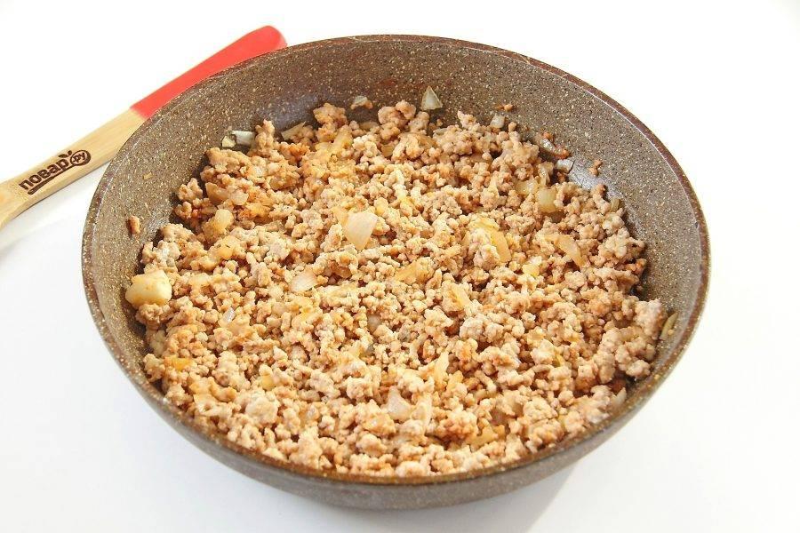 Обжарьте лук до мягкости, добавьте фарш, томатную пасту, соль и специи. Готовьте все вместе, периодически помешивая, около 5-7 минут.
