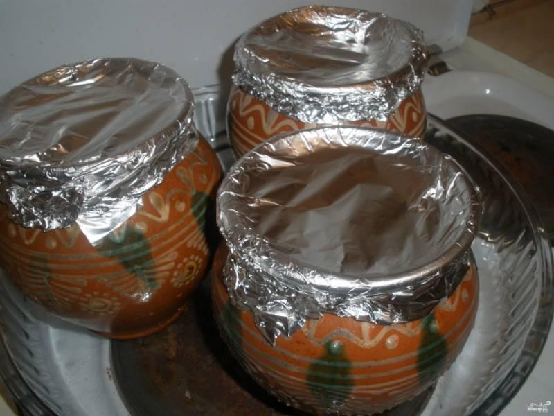 Закройте горшочки фольгой, отправьте их на два часа в разогретую до 180 градусов духовку.