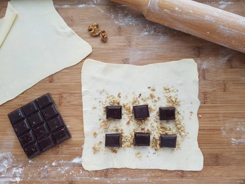 Свернуть штрудель можно двумя способами, классическим и косичкой. Для первого, раскатанное тесто присыпьте орехами, оставив по бокам пустую полоску в один-два сантиметра. Сверху уложите шоколад.