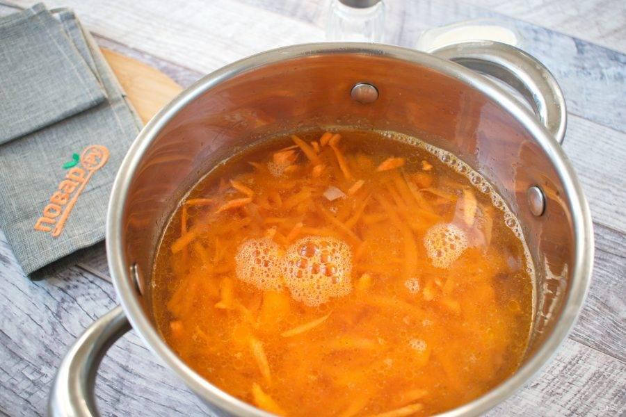 Добавьте морковь, натертую на крупной терке. Влейте горячую воду, посолите.